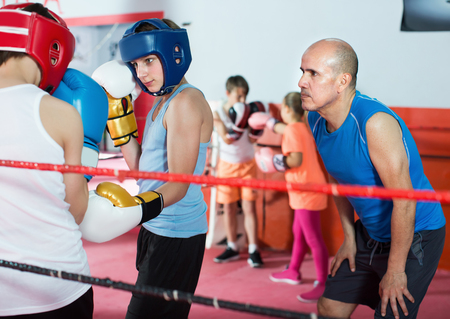 Boys sportsmans at boxing workout with instructor on boxing ring