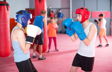 Two boys practice in sparring at boxing training Stock Photo