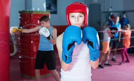fighting stance: Teenage boy boxer posing during boxing exercising at gym