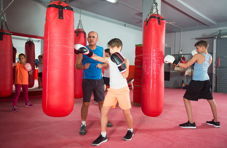shocks: Boys and a girl perform shocks exercises with a coach in boxing training
