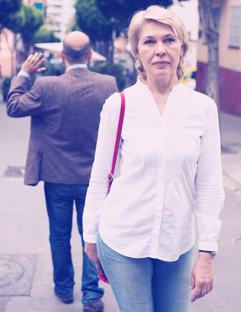 angry retiree blond woman being irritated with man standing back to her in town
