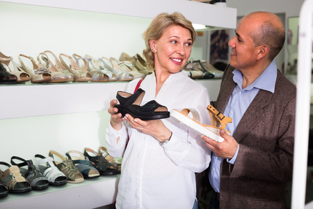 look latino: portrait of smiling elderly man and woman picking pair of shoes in boutique Stock Photo
