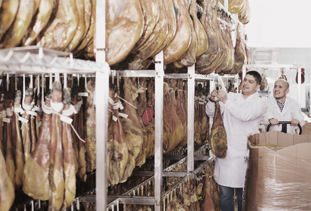 Mature butcher and his assistant with a jamon joints at a meat factory. Focus on young man
