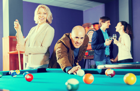 Positive people playing billiard and darts as hanging out
