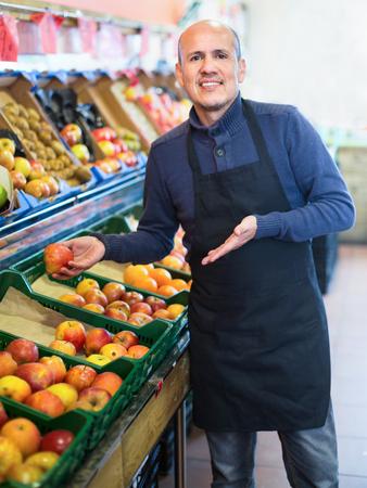 Elderly seller offering seasonal ripe fruits in local grocery