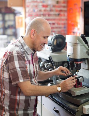 Sonriente trabajador maduro haciendo duplicados de llaves en la máquina láser