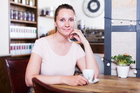 Smiling young woman sitting in cafe and drinking coffee for breakfast