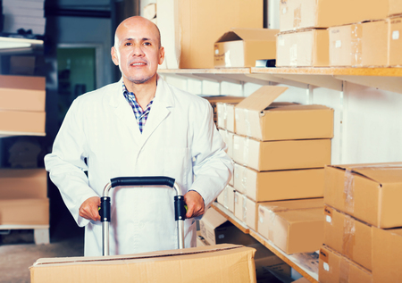Portrait of mature man standing with cart and carton boxes