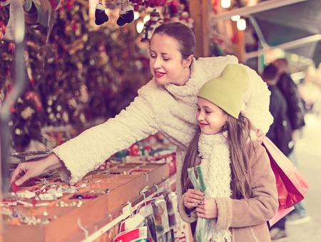 overspending: Smiling happy mother with daughter choosing gifts in Christmas market
