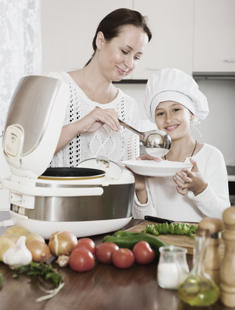 Happy mother and little daughter using multicooker for cooking vegetables at kitchen