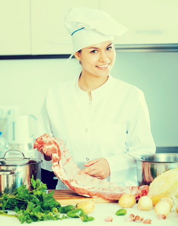 Happy female chef working with pork ribs in kitchen