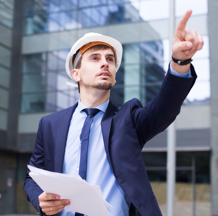 Man in helmet with documents pointing finger to object Stock Photo