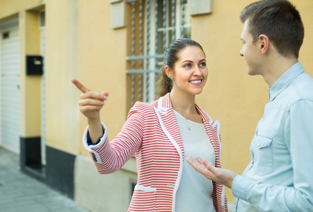 sidewalk talk: Cheerful young brunette helping lost male tourist to find way Stock Photo