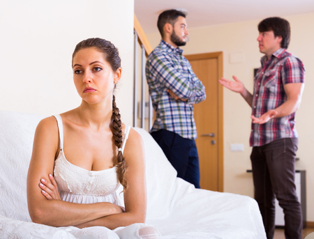 Sad girl and two men at home: problems of love triangle Stock Photo