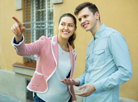 sidewalk talk: Traveller asking happy woman to show him direction. Focus on man Stock Photo