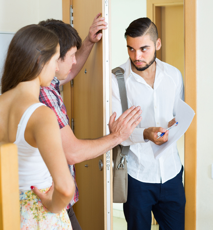 Agent clamouring credit repayment from couple at the doorway