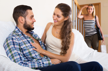 Love triangle: happy husband, upset wife and lover at home interior