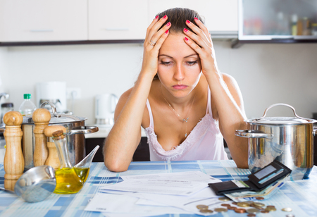 in low spirits: Portrait of worry girl with dicuments and money Stock Photo