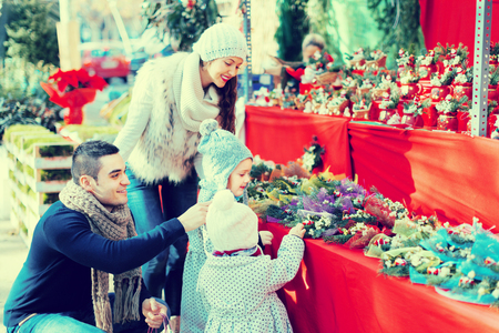 5s: Young smiling parents with little girls at counter with Poinsettia. Shallow focus