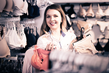Young american female customer showing her purchases in underwear shop