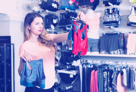 acquiring: Shopper is choosing sports underwear in lingerie shop.
