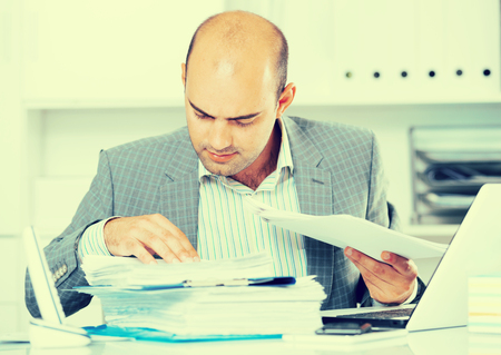 positiv: Young and smiling businessman in shirt viewing documents at the table