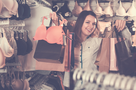 happy european  female customer showing her purchases in underwear shop