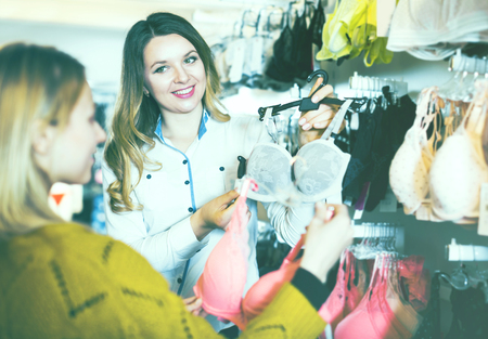 Positive young woman seller assisting woman in choosing bra in underwear store Stock Photo