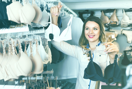 acquiring: Young woman shopper examining bras in underwear shop