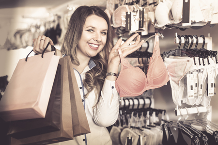 Smiling  pleasant  female shopper boasting her purchases in underwear shop
