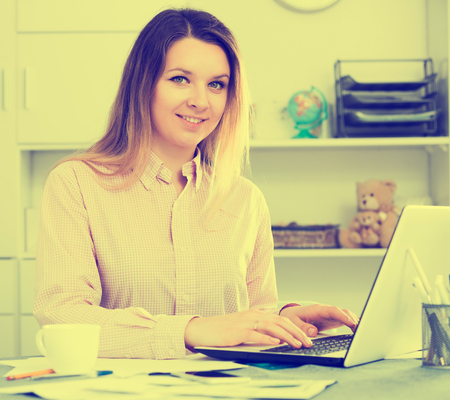 expertize: Positive adult female employee having productive day at work in office
