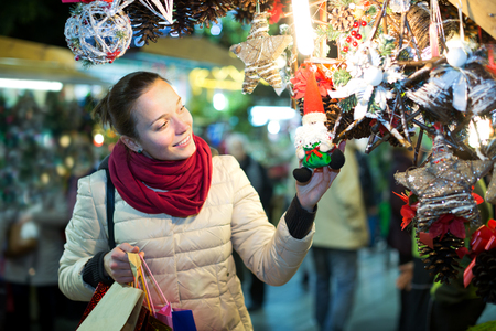 lifestile: Portrait of smiling young woman customer near counter with Christmas gifts in evening time