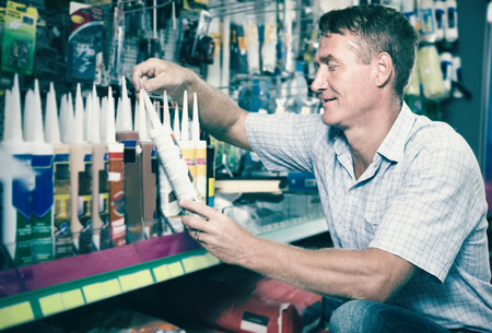 sealant: concentrated man customer choosing sealant tube in housewares hypermarket