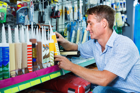 sealant: Portrait of positive cheerful male customer selecting sealant bottle in housewares department