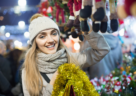 Portrait of young positive cheerful  woman in coat posing at Xmas fair in evening