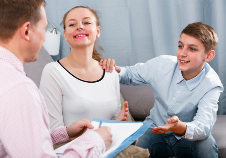 Smiling mother and son preparing beneficial agreement papers at home