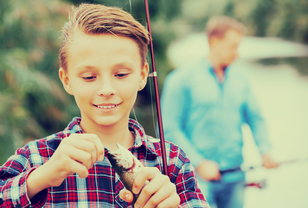 Glad teenager boy holding and looking at fish on hook Stock Photo