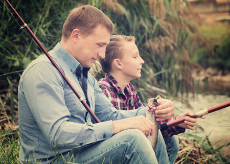 Glad father and teenager son fishing together from the water side at a river. Focus on man