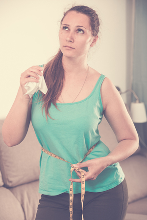 Sad young woman measuring waist after weight gain at home