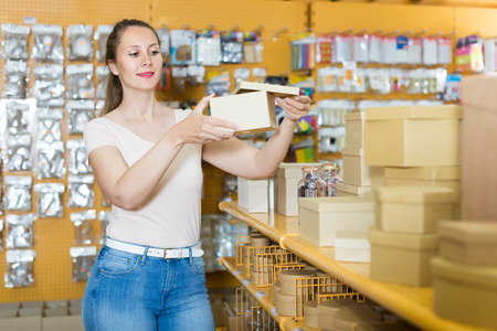 Ordinary girl with gift boxes in her hands in store