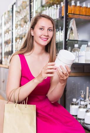 choise: Smiling blonde young woman take a choise shampoo in perfume supermarke