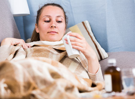 Young woman having cold and taking medicine at home