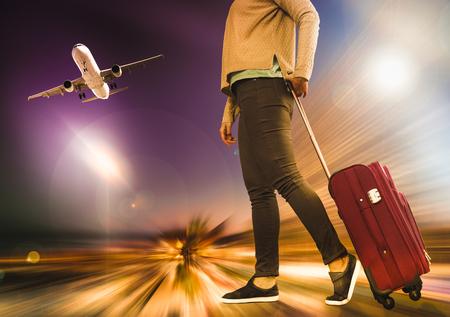 여자는 짐과 비행기 배경에 짐을 운반한다. 스톡 콘텐츠