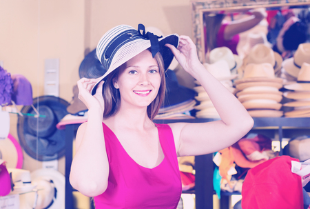 Happy cheerful  young  female try on rose floppy hat in botique Stock Photo