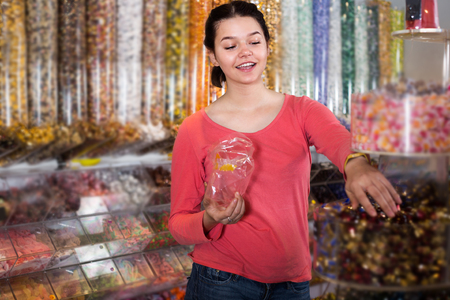 Girl in store is picking up candies by hands into package. Stock Photo