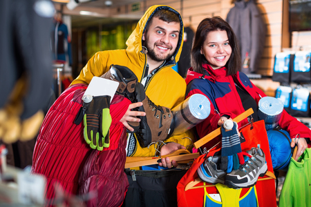 boasting: Young happy demonstrating new tourist equipment in sports clothes store Stock Photo