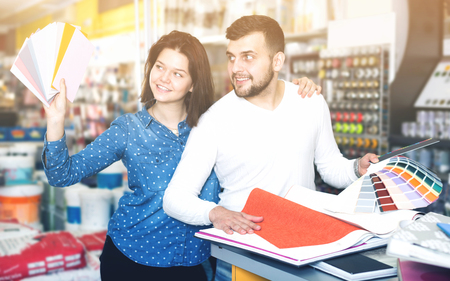 Cheerful young couple examining color scheme variants in paint supplies supermarket