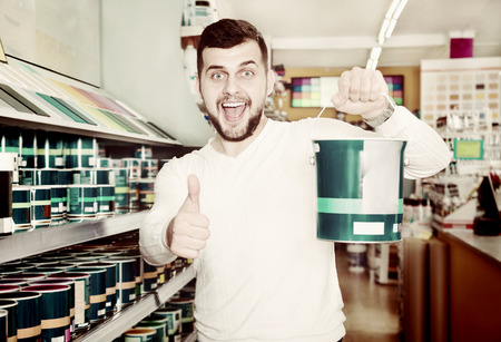 coatings: Male customer examining various wall paints at paint supplies store Stock Photo