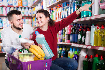 two positive adult people in good spirits selecting detergents ?n the shelves in the store