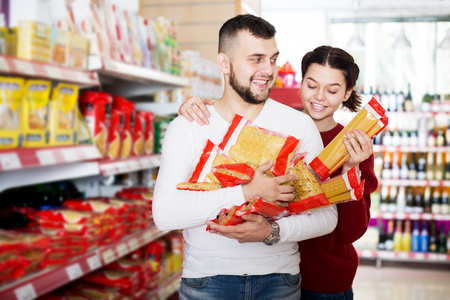 Smiling adults reading lable of pasta at supermarket